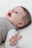 Happy baby girl lying on back over white bedcover Stock Photos