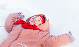 Baby girl lying down on the snow Stock Photo