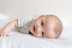 Happy baby girl lying down on white bed Stock Images