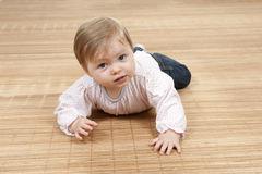 Happy baby girl lying on the floor Royalty Free Stock Image