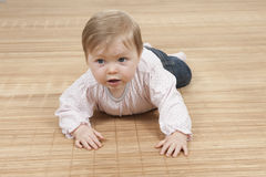 Happy baby girl lying on the floor Stock Photo