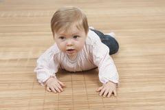 Happy baby girl lying on the floor Stock Photo