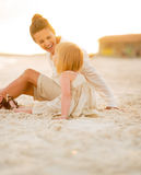 Happy baby girl and mother sitting on the beach Stock Photography
