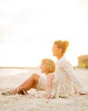 Happy baby girl and mother sitting on the beach Stock Images