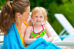 Happy baby girl with mother sitting on sunbed Stock Images