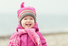 Happy baby girl in a pink hat and scarf Royalty Free Stock Photos