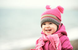 Happy baby girl in pink hat and scarf laughs. Happy baby girl in a pink hat and scarf laughs royalty free stock photos