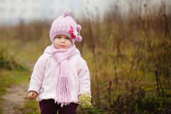 Happy baby girl in a pink hat and scarf laughs Stock Photo