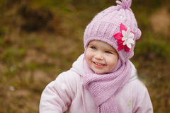 Happy baby girl in a pink hat and scarf laughs in autumn Royalty Free Stock Images