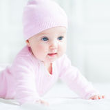 Happy baby girl in a pink knitted hat. Happy smiling baby girl in a pink knitted hat Royalty Free Stock Photo