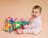Happy baby girl played with color blocks Royalty Free Stock Images