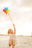 Happy baby girl playing with colorful windmill toy Royalty Free Stock Photos