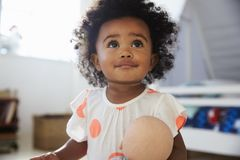 Happy Baby Girl Playing With Doll In Playroom Stock Photography