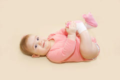 Happy baby girl playing with her feet Stock Images