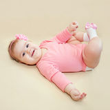 Happy baby girl playing with her feet Stock Photography