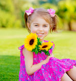 Happy baby girl. Playing outdoor, cute child holding fresh sunflower flowers, kid having fun in summer park, lovely smiling toddler portrait, enjoying nature of Stock Images