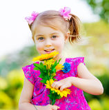Happy baby girl. Playing outdoor, cute child holding fresh sunflower flowers, kid having fun in summer park, lovely smiling toddler portrait, enjoying nature of Royalty Free Stock Photos