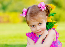 Happy baby girl. Playing outdoor, cute child holding fresh sunflower flowers, kid having fun in summer park, lovely smiling toddler portrait, enjoying nature of Stock Photo