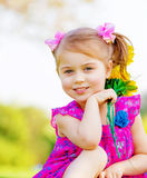 Happy baby girl. Playing outdoor, cute child holding fresh sunflower flowers, kid having fun in summer park, lovely smiling toddler portrait, enjoying nature of Royalty Free Stock Photo
