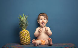 Happy baby girl playing with a pineapple Stock Photo