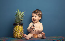Happy baby girl playing with a pineapple Royalty Free Stock Photo
