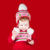 Happy baby girl playing with red Christmas bow Royalty Free Stock Photo