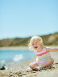 Happy baby girl playing with sand on beach Royalty Free Stock Photography