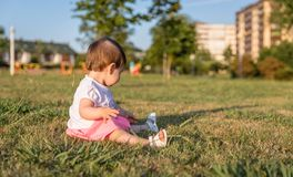 Happy baby girl playing sitting on a grass park Royalty Free Stock Image