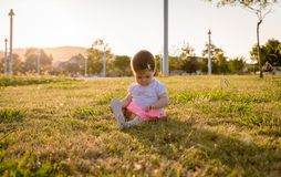 Happy baby girl playing sitting on a grass park Royalty Free Stock Photos