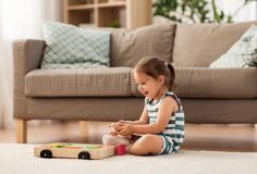 Happy baby girl playing with toy blocks at home. Childhood and people concept - happy three years old baby girl playing with toy blocks at home royalty free stock image