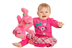 Happy baby girl plays with pink teddy bear. Happy active baby girl waves and holds pink teddy bear upside down. She wears pink shirt and tights with plaid skirt Stock Photography