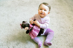 Happy baby girl plays with toy bear Royalty Free Stock Image