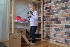 Happy baby girl is putting clothes in cardboard box stock image