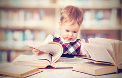 Happy baby girl reading a book in a library Royalty Free Stock Images