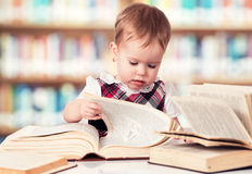 Happy baby girl reading a book in a library Stock Images