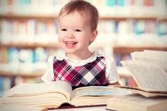 Happy baby girl reading a book in a library Royalty Free Stock Image