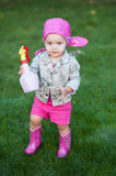 Happy baby girl in red boots walking on the meadow Royalty Free Stock Photos