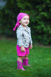 Happy baby girl in red boots walking on the meadow Stock Photos