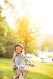 Happy baby girl riding bicycle outdoors Stock Images