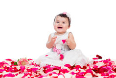 Happy baby girl among rose petals Royalty Free Stock Images