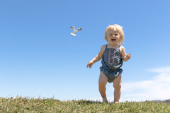 Happy baby girl runs on top of the hill Royalty Free Stock Images