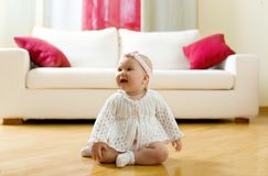 Happy baby girl seated on a hardwood floor Royalty Free Stock Photography