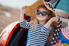 Happy baby girl sitting in the car trunk Royalty Free Stock Photos
