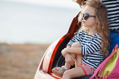 Happy baby girl sitting in the car trunk. Vacation, Travel - family ready for the travel for summer vacation. suitcases and car with sea on background. girl with Royalty Free Stock Photography