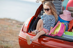 Happy baby girl sitting in the car trunk Royalty Free Stock Images