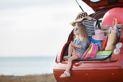 Happy baby girl sitting in the car trunk. Vacation, Travel - family ready for the travel for summer vacation. suitcases and car with sea on background. girl with Stock Photos