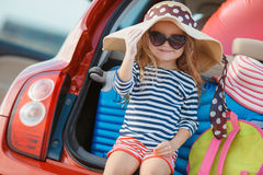 Happy baby girl sitting in the car trunk Stock Photos