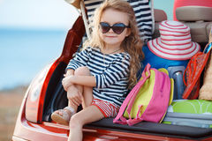 Happy baby girl sitting in the car trunk Royalty Free Stock Photography