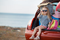 Happy baby girl sitting in the car trunk Stock Photo