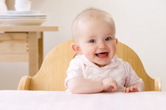 Happy baby girl sitting in high chair Royalty Free Stock Photo